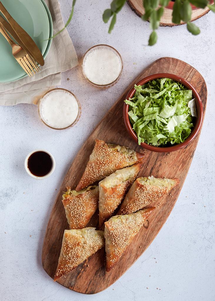 Samose složene na drvenoj dasci, zdjela salate i dvije čaše piva.